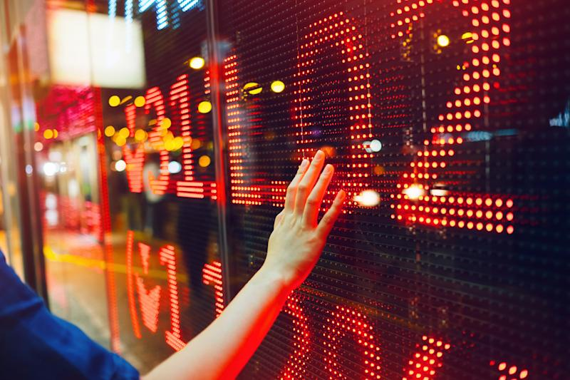 Woman's hand on stock exchange market display screen board on the street showing stock drops in red colour