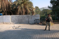 An army soldier inspects the scene of the rocket attack at the gate of al-Zawra public park in Baghdad, Iraq, Wednesday, Nov. 18, 2020. Rockets struck Iraq's capital on Tuesday with four landing inside the heavily fortified Green Zone, Iraq's military said, killing a child and wounding at least five people, signaling an end to an informal truce announced by Iran-backed militias in October.(AP Photo/Khalid Mohammed)
