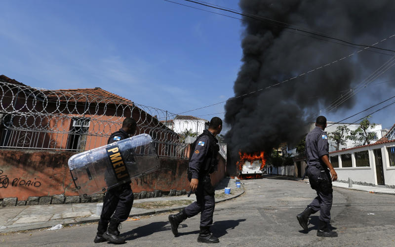 Policemen walk past a burning bus set on fire by residents of the Telerj slum as they attempt to repossess the land in Rio de Janeiro, April 11, 2014. About 5,000 people were evicted by the police after they occupied the site, which belongs to telecoms group Oi, since March 31. REUTERS/Sergio Moraes (BRAZIL - Tags: CIVIL UNREST SOCIETY POVERTY TPX IMAGES OF THE DAY)