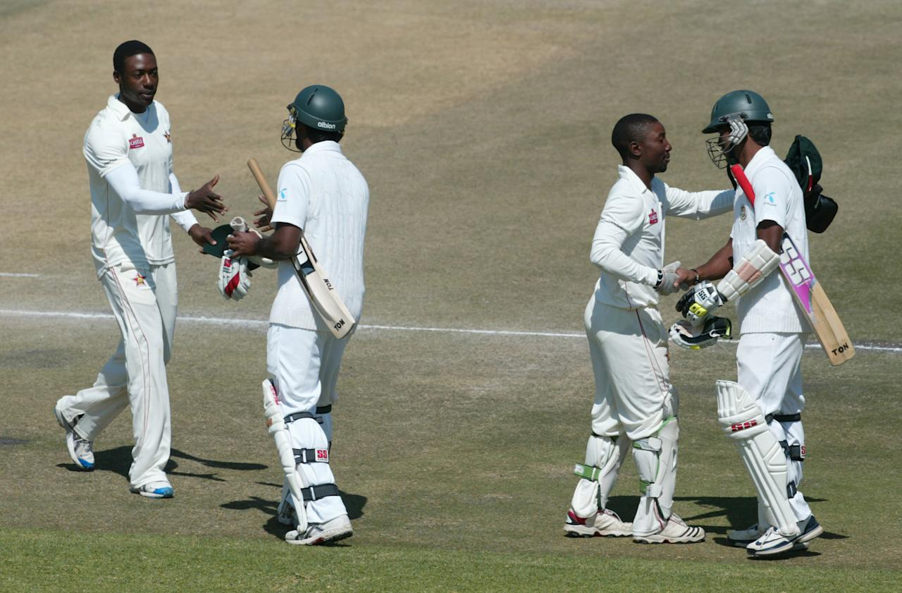 Zimbabwe's players Vusimusi Sibanda (L) and Tatenda Taibu (R) commiserate with Bangladesh's batsmen Rubel Hossain and Robiul Islam after their victory by 130 runs in a one-off Test cricket match at Harare Sports club on August 8, 2011.    AFP PHOTO / JEKESAI NJIKIZANA (Photo credit should read JEKESAI NJIKIZANA/AFP/Getty Images)