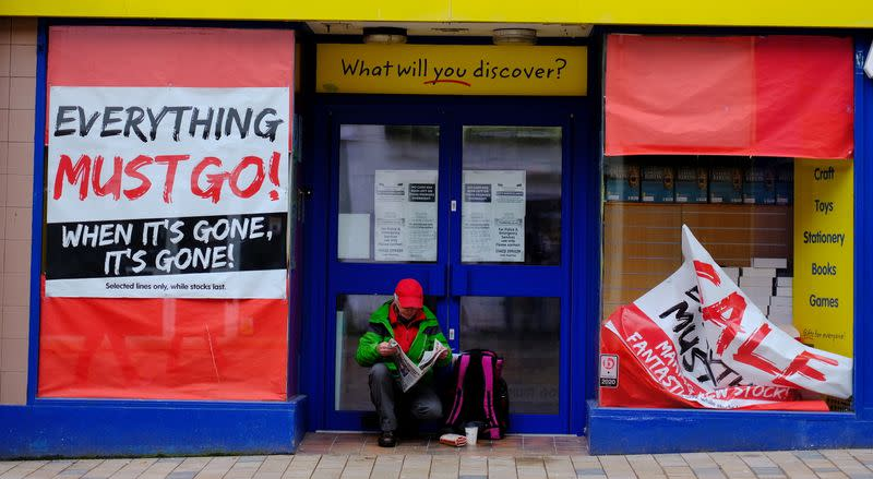 A man reads a newspaper as he sits in the door of a closed retail unit in Blackpool