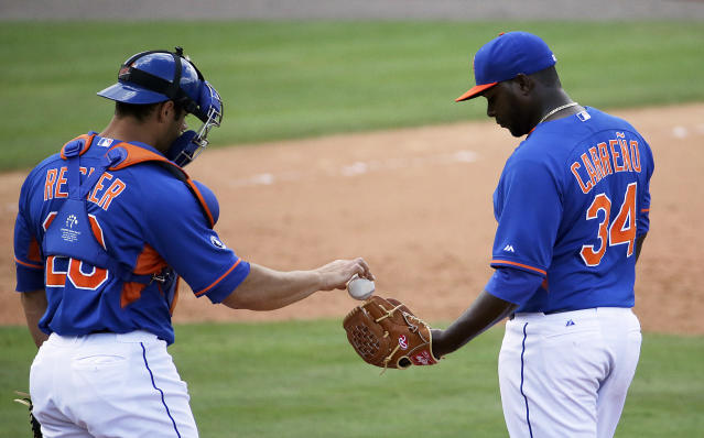 New York Mets relief pitcher Joel Carreno, right, is handed the ball by catcher Anthony Recker after Carreno walked St. Louis Cardinals' Stephen Piscotty to score teammate Scott Moore in the eighth inning of an exhibition spring training baseball game, Wednesday, March 12, 2014, in Port St. Lucie, Fla. (AP Photo/David Goldman)