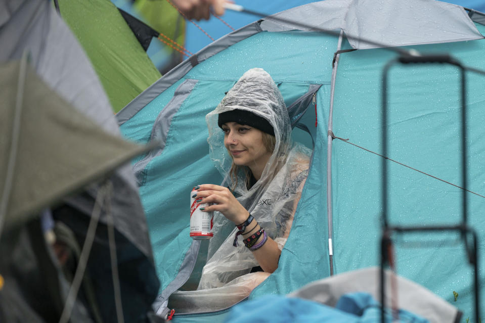 A festivalgoers shelters from the rain on the first day of Download Festival at Donington Park at Castle Donington, England, Friday June 18, 2021. The three-day music and arts festival is being held as a test event to examine how Covid-19 transmission takes place in crowds, with the the capacity significantly reduced from the normal numbers. (Joe Giddens/PA via AP)