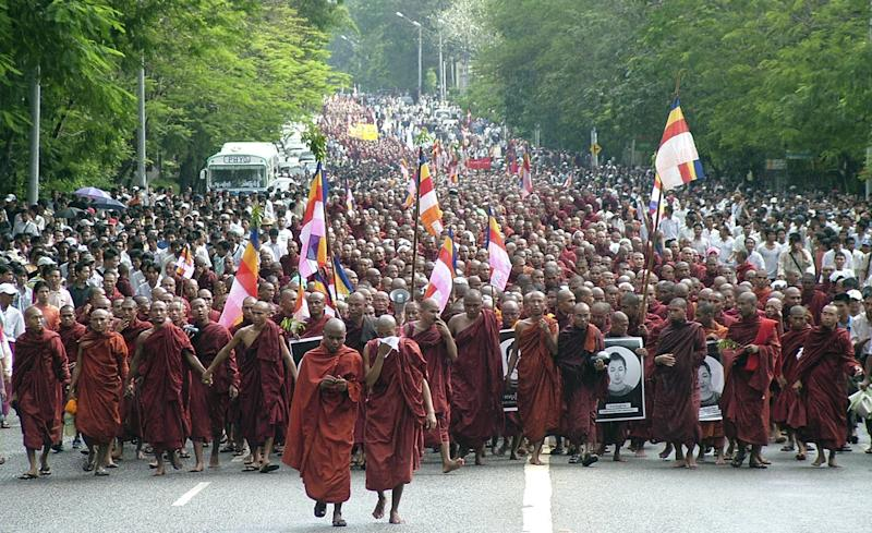 FILE - In this Sept. 24, 2007 file photo, Buddhist monks march on a street in protest against the military government in Yangon, Myanmar. President Barack Obama's historic visit to Myanmar on Monday, Nov. 19, 2012 is meant to show America's support for the country's transition to democracy. Obama's roughly six-hour visit will be confined to Yangon, the main city where the military brutally crushed pro-democracy uprisings in the past, including a 2007 rally led by Buddhist monks and protests in 1988 led by student activists. (AP Photo/File)