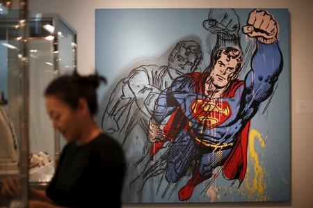 """FILE PHOTO: A woman stands in front of Andy Warhol's """"Superman"""", which is expected to fetch USD $6-8 million at a pre-auction viewing at Sotheby's in Los Angeles"""