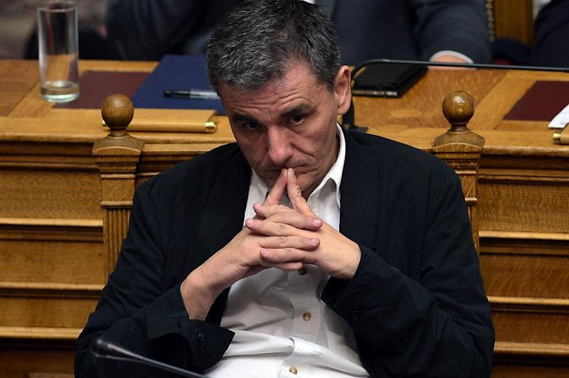 Greek Finance Minister Euclid Tsakalotos listens as Prime Minister Alexis Tsipras addresses a session at the Greek parliament in Athens early on July 23, 2015 (AFP Photo/Louisa Gouliamaki)