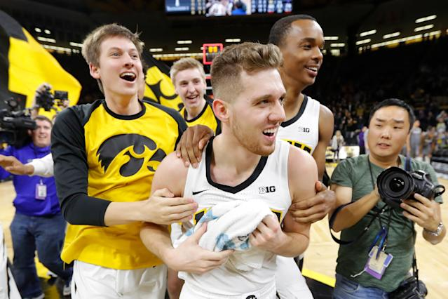 Iowa guard Jordan Bohannon, center, celebrates with teammates after hitting a three-point shot at the end of the game to beat Northwestern on Feb. 10, 2019, in Iowa City, Iowa. (AP)