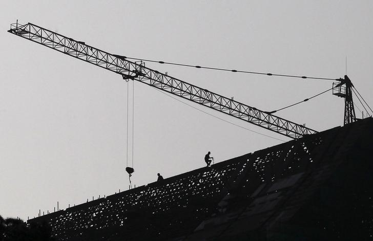 Labourers work on top of a construction site in Jinning