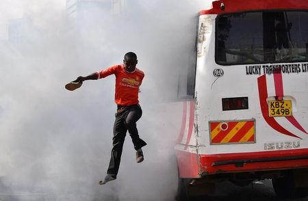 A supporter of Kenyan opposition leader Raila Odinga of the National Super Alliance (NASA) coalition jumps from a bus after riot police fired teargas canisters to disperse them after his swearing-in ceremony in Nairobi, Kenya January 30, 2018. REUTERS/Isaac Biosse