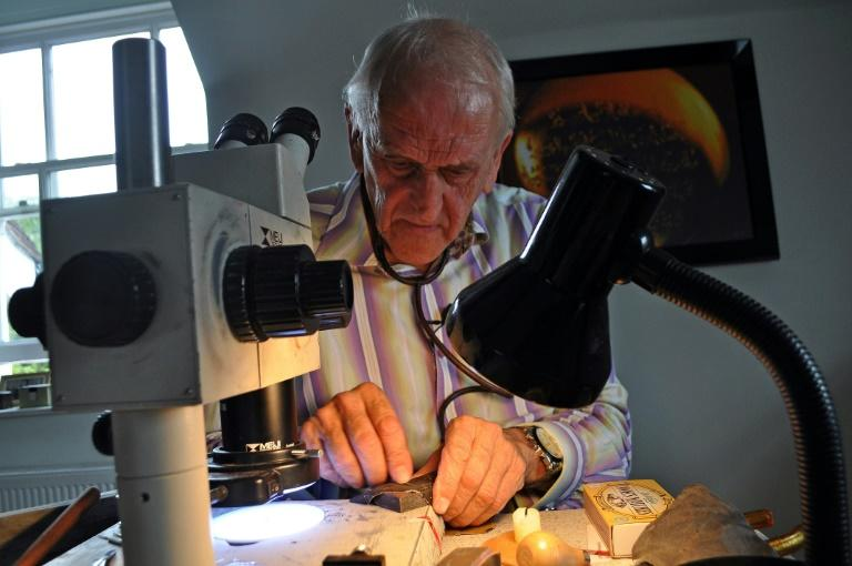Micro-engraver Graham Short works on engraving a pin head in his studio in Birmingham, central England