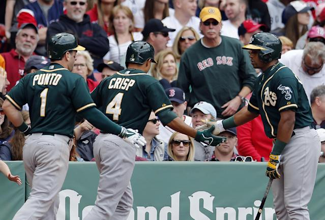 Oakland Athletics' Nick Punto (1) and Coco Crisp (4) celebrate after scoring on a double by Jed Lowrie in the ninth inning of a baseball game against the Boston Red Sox in Boston, Saturday, May 3, 2014. The Red Sox won 6-3. (AP Photo/Michael Dwyer)