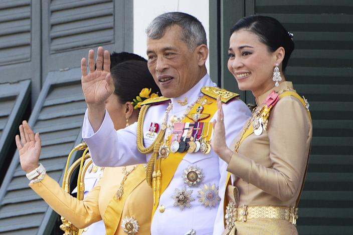 King Maha Vajiralongkorn and Queen Suthida wave to an audience