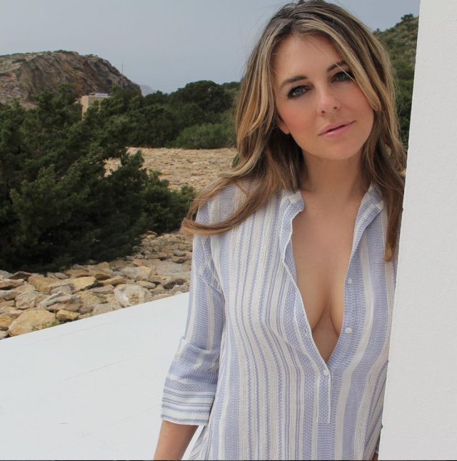 <p>The designer shared a photo on Intagram showing her line's Fregate shirt unbuttoned down to her midsection. The soft, textured cotton top has blue and white stripes. It seems like it would normally be worn over a bathing suit, but we're pretty sure Hurley's not wearing one here. (Photo: elizabethhurley1 via Instagram) </p>