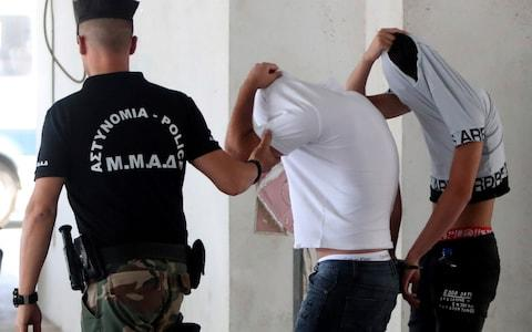 <span>Suspects cover their faces with their shirts as they arrive at the Famagusta courthouse in Paralamni, Cyprus, in July </span> <span>Credit: AP </span>