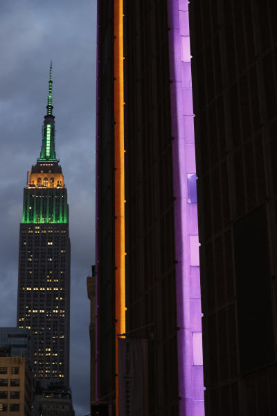 The side of Madison Square Garden, right, is illulminated in gold and purple, colors of the Los Angeles Lakers as the Empire State Building is shown nearby, Sunday, Jan. 26, 2020, in New York. The colors are in memory of retired Lakers star Lobe Bryant, who died in a helicopter crash earlier Sunday in California. (AP Photo/Kathy Willens)