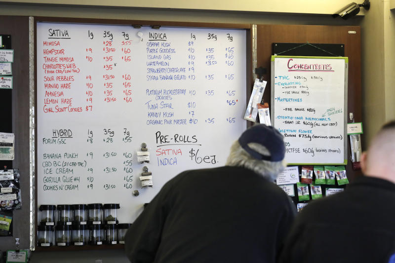 In this Wednesday, Oct. 9, 2019 photo, customers stand at a counter where prices of marijuana products are posted at the Medicinal Cannabis Dispensary, an unlicensed marijuana shop, in Vancouver, B.C. (AP Photo/Elaine Thompson)