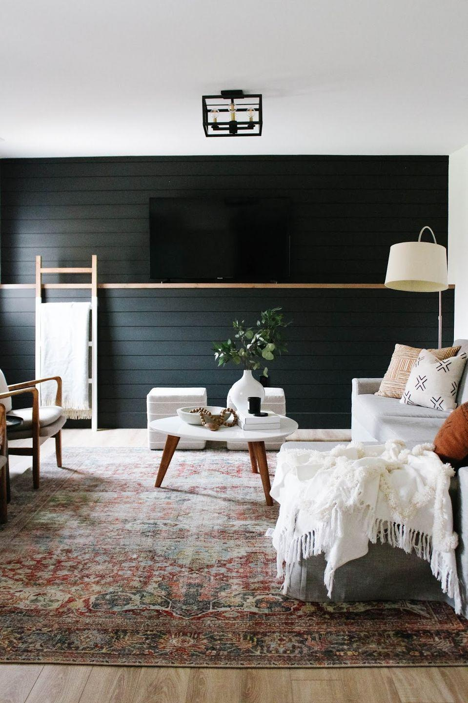 """<p>Step outside your comfort zone by featuring bold black shiplap walls in your basement. This look pairs well with neutrals and is the most genius way to hide your TV in plain sight!</p><p><strong>See more at <a href=""""https://www.houseofhiredesigns.com/2019/10/basement-reveal.html"""" rel=""""nofollow noopener"""" target=""""_blank"""" data-ylk=""""slk:House of Hire"""" class=""""link rapid-noclick-resp"""">House of Hire</a>.</strong></p><p><a class=""""link rapid-noclick-resp"""" href=""""https://go.redirectingat.com?id=74968X1596630&url=https%3A%2F%2Fwww.walmart.com%2Fip%2F15-W-x-48-H-x-3-1-2-D-Vintage-Farmhouse-3-Rung-Ladder-Barnwood-Decor-Collection-Reclaimed-Grey%2F256880278&sref=https%3A%2F%2Fwww.thepioneerwoman.com%2Fhome-lifestyle%2Fdecorating-ideas%2Fg34763691%2Fbasement-ideas%2F"""" rel=""""nofollow noopener"""" target=""""_blank"""" data-ylk=""""slk:SHOP DECORATIVE LADDERS"""">SHOP DECORATIVE LADDERS</a></p>"""