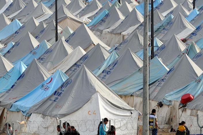 Syrian refugees walk among tents at Karkamis' refugee camp on January 16, 2014 near the town of Gaziantep, in southern Turkey (AFP Photo/Ozan Kose)