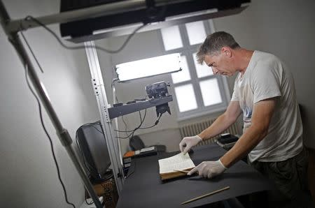 Photographer Jim Marshall, a member of the Foundation for the Preservation of Historical Heritage, photographs pages of a book in Bosnia's National Library in Sarajevo August 19, 2014. REUTERS/Dado Ruvic