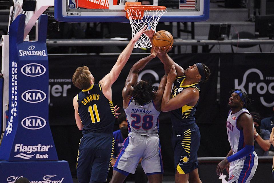 Detroit Pistons center Isaiah Stewart (28) drives to the basket against Indiana Pacers forward Domantas Sabonis (11) and center Myles Turner (33) during the third quarter at Little Caesars Arena in Detroit on Thursday, Feb. 11, 2021.