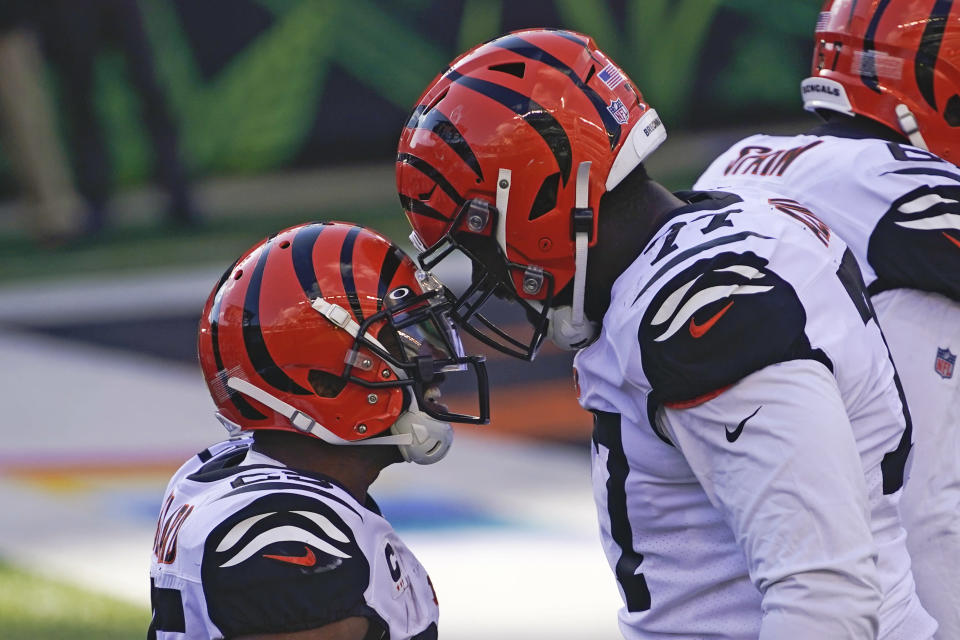 Cincinnati Bengals' Giovani Bernard (25) celebrates rushing for a touchdown with Hakeem Adeniji (77) during the first half of an NFL football game against the Tennessee Titans, Sunday, Nov. 1, 2020, in Cincinnati. (AP Photo/Bryan Woolston)