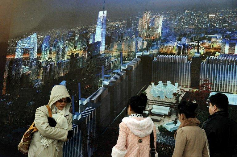 Commuters walk past a billboard showing a property development in central Beijing, on December 14, 2011