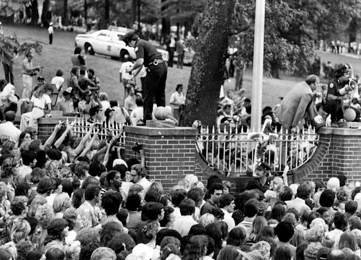 Police estimated that 50,000 - 100,000 people turned out at Graceland to pay their respects the day after Elvis died. (PA)