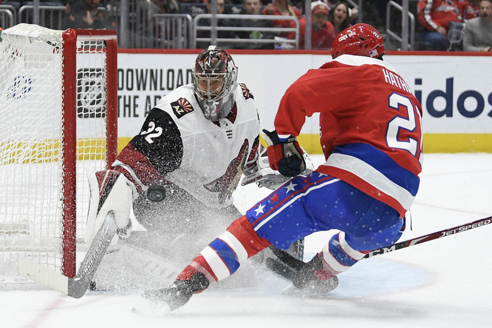 Washington Capitals right wing Garnet Hathaway (21) tries to get the puck past Arizona Coyotes goaltender Antti Raanta (32), of Finland, during the second period of an NHL hockey game, Monday, Nov. 11, 2019, in Washington. (AP Photo/Nick Wass)
