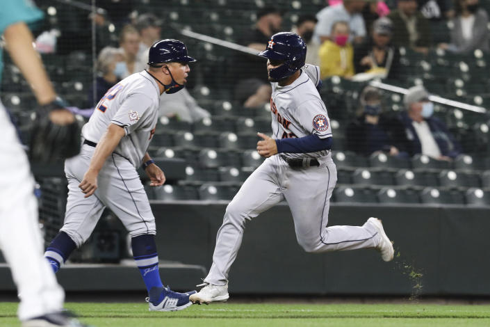 Houston Astros' Alexander De Goti rounds third on the way to scoring on a double by Chas McCormick during the fifth inning of the team's baseball game against the Seattle Mariners on Friday, April 16, 2021, in Seattle. (AP Photo/Jason Redmond)