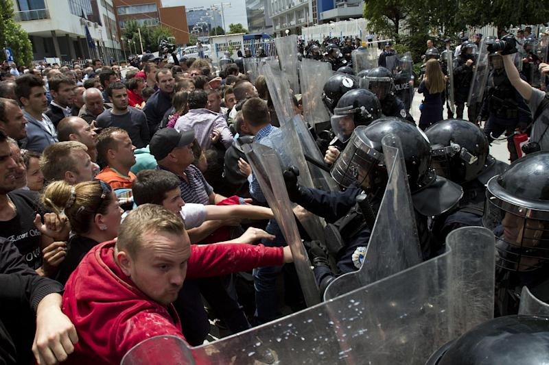 Kosovo police face hardline opposition members protesting a deal with Serbia in capital Pristina, Kosovo, Thursday, June 27, 2013. Kosovo lawmakers voted in favor of an agreement to normalize relations with Serbia.( AP Photo / Visar Kryeziu )