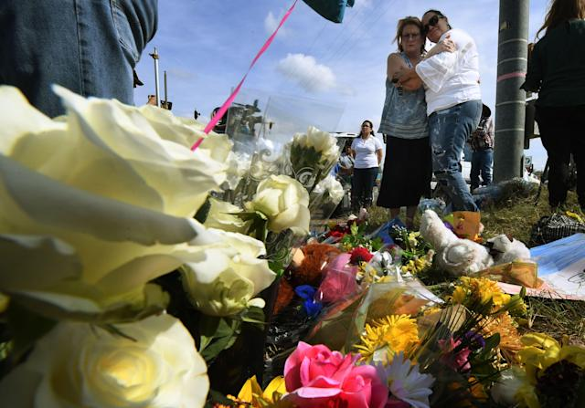 <p>Brenda Woldridge (L) and Meredith Cooper embrace at a memorial outside the First Baptist Church, after a mass shooting that killed 26 people in Sutherland Springs, Texas on Nov. 7, 2017. (Photo: Mark Ralston/AFP/Getty Images) </p>
