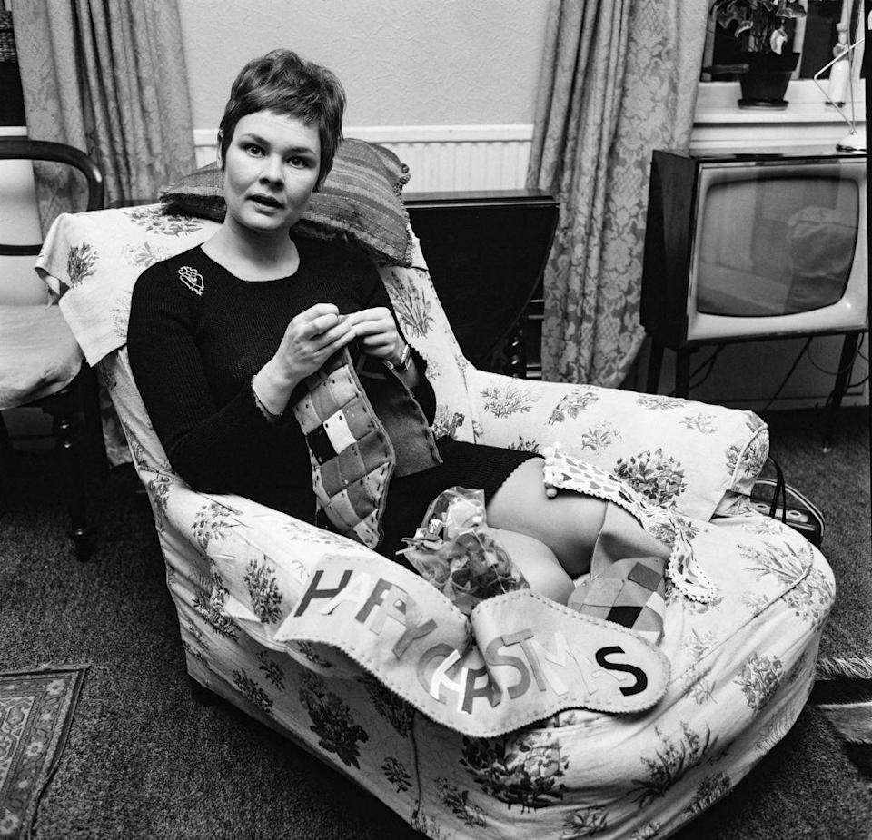 <p>The English actress gets cozy as she sews Christmas stockings for her nephews in December of 1967.</p>