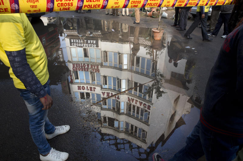 In this Tuesday, Feb. 12, 2019, file photo, The Arpit Palace Hotel is reflected in a puddle after an early morning fire at the hotel killed more than a dozen people in the Karol Bagh neighborhood of New Delhi, India. (AP Photo/Manish Swarup, File)