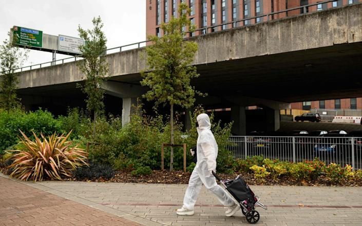 A student wearing full-body PPE due to the COVID-19 pandemic, walks towards the Coventry University Library at the beginning of the new academic year,at Coventry University, in Coventry, central England on September 23, 2020 - Oli Scarff/AFP
