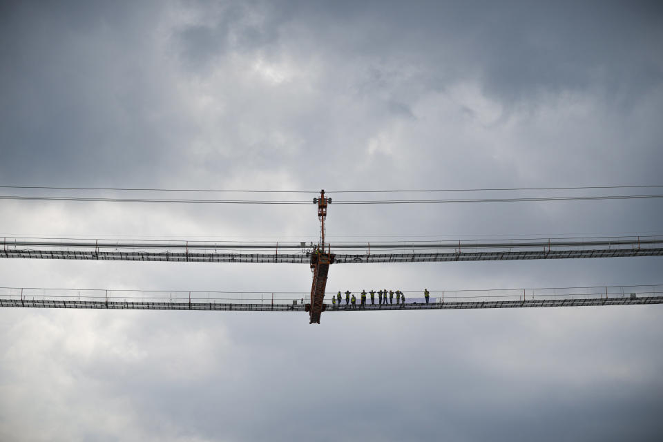 Workers stand on the structure during a ceremony marking 100 years of diplomatic relations between Japan and Romania, at the construction site of a suspension bridge over the Danube river in Braila, Romania, Thursday, Aug. 26, 2021. The bridge, built by Japanese and Italian companies, with a span of 1,974.3 meters, will be the largest of its kind in Romania and the third in the European union.(AP Photo/Vadim Ghirda)