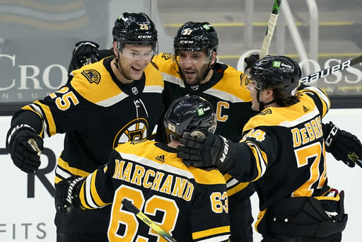 Boston Bruins defenseman Brandon Carlo (25) celebrates his goal with teammates Patrice Bergeron (37), Jake DeBrusk (74), and Brad Marchand (63) in the third period of an NHL hockey game against the Philadelphia Flyers, Thursday, Jan. 21, 2021, in Boston. (AP Photo/Elise Amendola)