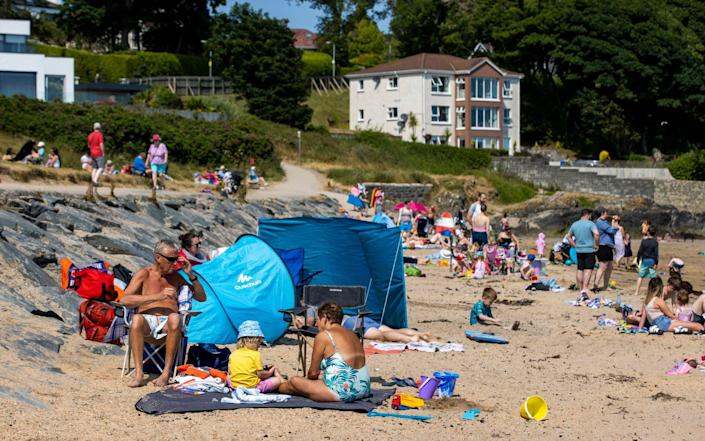 People enjoying the sun at Helen's Bay beach in County Down, Northern Ireland - Liam McBurney/PA Wire