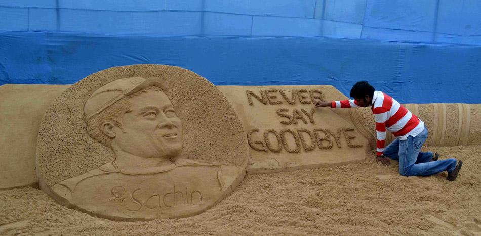 "Indian sand artist Sudarsan pattnaik gives the final touches to his sand sculpture of Indian cricketer Sachin Tedulkar with the message ""Never say Goodbye"" at Cuttack, some 25 kilometers from Bhubaneswar on November 16, 2013.  Indian cricket legend Sachin Tendulkar wept as he left the pitch for the final time after his 200th Test match, ending a dazzling career spanning nearly a quarter of a century.   AFP PHOTO/ASIT KUMAR"