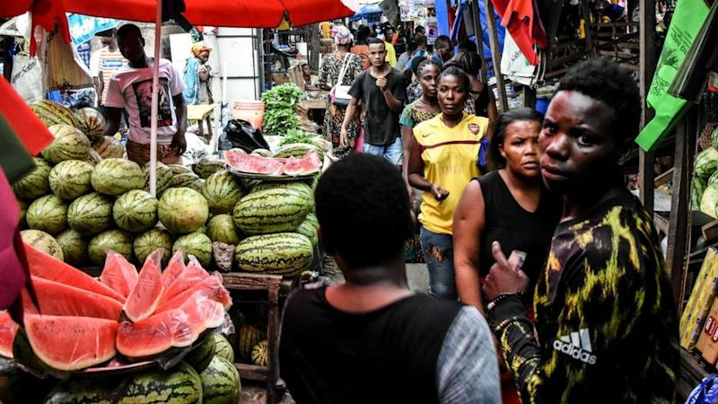People walk at a market without adhering to the rules of social distancing despite the confirmed Covid-19 coronavirus cases in Dar es Salaam, Tanzania, on April 15, 2020.