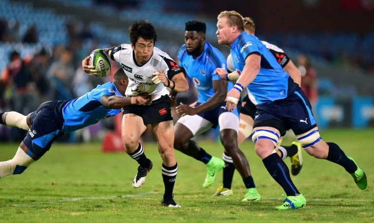 Warrick Gelant (L) of the Blue Bulls tackles Takaaki Nakazuru (C) of the Sunwolves during their Super XV rugby union match on March 17, 2017 in Pretoria, South Africa