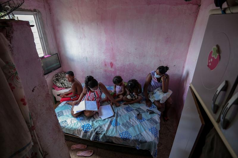 Student Gloria Dayane (2nd L), next to her mother Darla da Silva (R), 31 and her three siblings does her homework on a printed pdf version of a textbook, at the Vila da Fabrica neighborhood in Camaragibe, Pernambuco state, Brazil, on July 25, 2020, during the COVID-19 pandemic. - Science teacher Arthur Cabral rides his bike from the city of Recife to deliver pdf printed versions of textbooks for students without internet access, hence unable to attend online classes. Since last May, public schools have been closed within measures to combat the spread of the coronavirus pandemic. (Photo by Leo Malafaia / AFP) (Photo by LEO MALAFAIA/AFP via Getty Images)