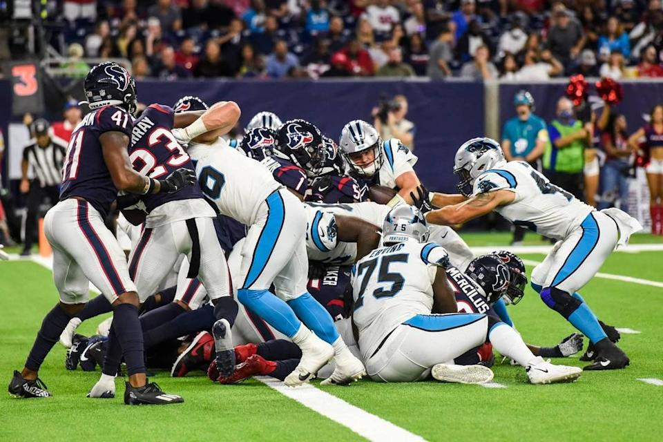 Panthers quarterback Sam Darnold, second from back right, pushes through the scrum toward the end zone in the fourth quarter Thursday. Darnold made it into the end zone to score a 1-yard touchdown, giving the Panthers their third touchdown and sealing their victory over the Texans, 24-9.