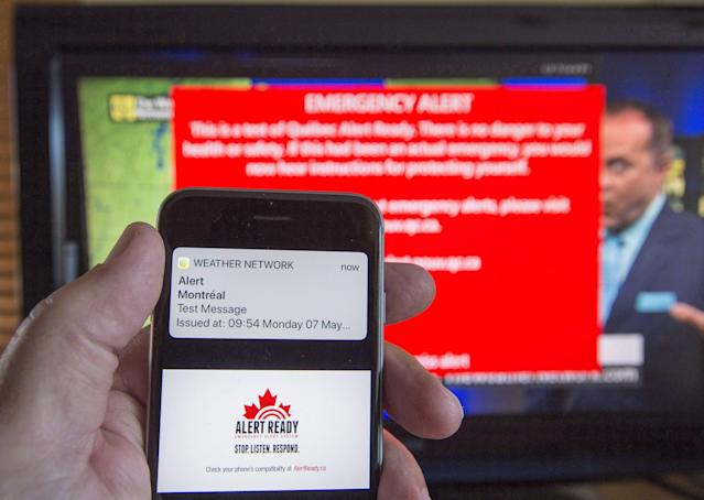 A smartphone and a television receive visual and audio alerts to test Alert Ready, a national public alert system, in Montreal on Monday, May 7, 2018. (THE CANADIAN PRESS/Ryan Remiorz)