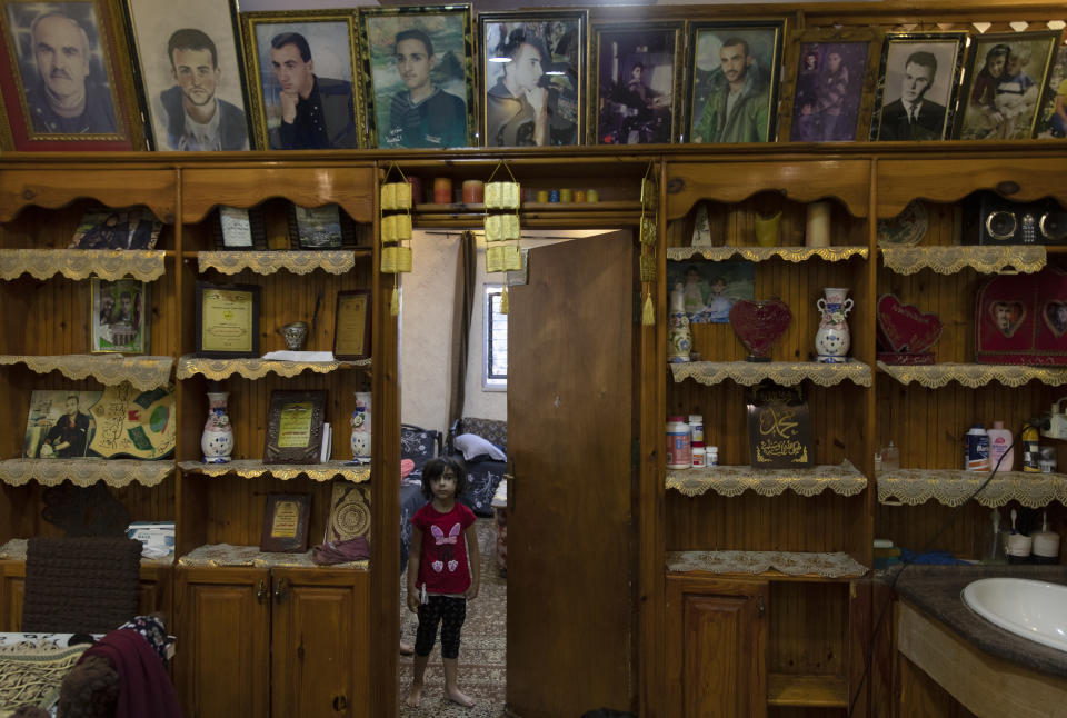 A Palestinian girl stands under framed portraits of family members, some of them were killed by the Israeli army according to Bahjat al-Alami, the grandfather of slain Mohammed al-Alami, 12, at the family house, in the West Bank village of Beit Ummar, near Hebron, Wednesday, Aug. 4, 2021. (AP Photo/Nasser Nasser)