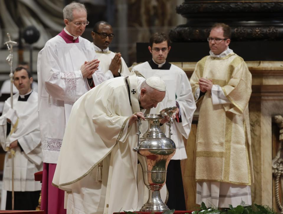 Pope Francis blows inside an amphora containing holy oil during a Chrism Mass inside St. Peter's Basilica, at the Vatican, Thursday, April 18, 2019. During the Mass the Pontiff blesses a token amount of oil that will be used to administer the sacraments for the year. (AP Photo/Alessandra Tarantino)