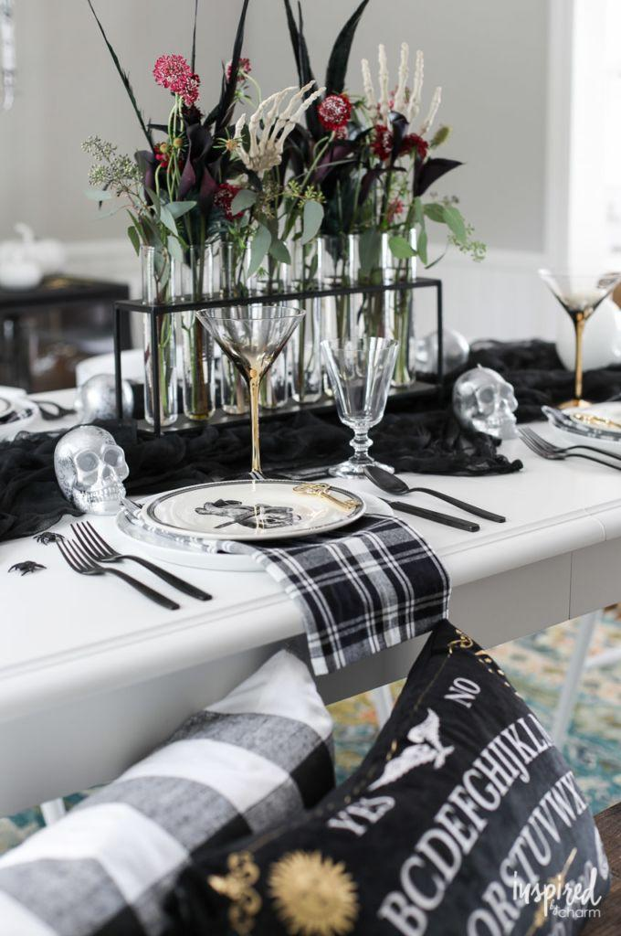 """<p>Go bare bones—this table centerpiece starts with a black runner base, topped with skulls and a spooky skeleton hand-infused flower display. The test-tube-style vase and dark blooms only enhance the eerie ambience. </p><p><strong>Get the tutorial at <a href=""""https://inspiredbycharm.com/spooky-chic-halloween-table-decorations/"""" rel=""""nofollow noopener"""" target=""""_blank"""" data-ylk=""""slk:Inspired by Charm"""" class=""""link rapid-noclick-resp"""">Inspired by Charm</a>. </strong></p><p><strong><a class=""""link rapid-noclick-resp"""" href=""""https://www.amazon.com/Creative-Co-op-Metal-Glass-Jointed/dp/B01L52PP88/?tag=syn-yahoo-20&ascsubtag=%5Bartid%7C10050.g.3739%5Bsrc%7Cyahoo-us"""" rel=""""nofollow noopener"""" target=""""_blank"""" data-ylk=""""slk:SHOP TEST TUBE VASES"""">SHOP TEST TUBE VASES</a><br></strong></p>"""