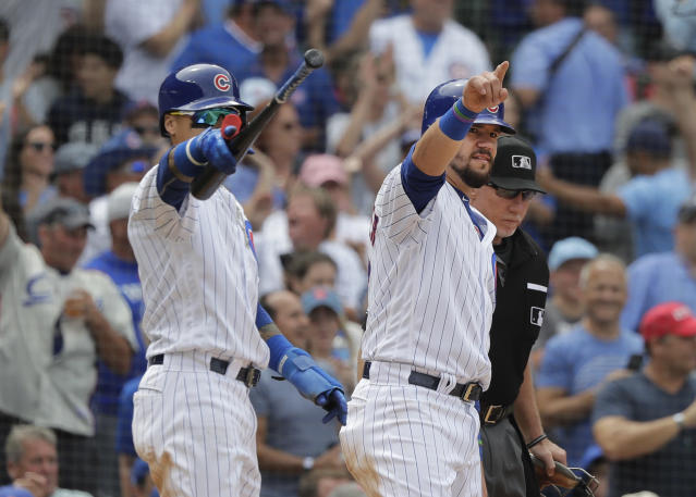 Chicago Cubs' Javier Baez, left, and Kyle Schwarber acknowledge Tommy La Stella at first after the pair scored on La Stella's single during the seventh inning of a baseball game against the St. Louis Cardinals Saturday, July 21, 2018, in Chicago. (AP Photo/Charles Rex Arbogast)
