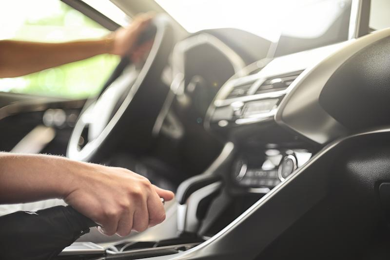 The man sits behind the wheel of a passenger car and pulls the handbrake. concept people and safety