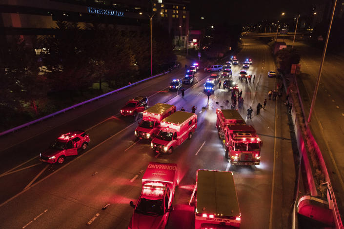 Emergency personnel work at the site where a driver sped through a protest-related closure on the Interstate 5 freeway in Seattle, authorities said early Saturday, July 4, 2020. Dawit Kelete, 27, has been arrested and booked on two counts of vehicular assault. (James Anderson via AP)