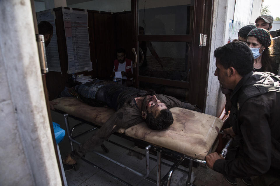 A man wounded in Turkish shelling is brought to Tal Tamr hospital in north Syria, Monday, Oct. 14, 2019. Syrian government troops moved into towns and villages in northern Syria on Monday, setting up a potential clash with Turkish-led forces advancing in the area as long-standing alliances in the region begin to shift or crumble following the pullback of U.S. forces. (AP Photo/Baderkhan Ahmad)